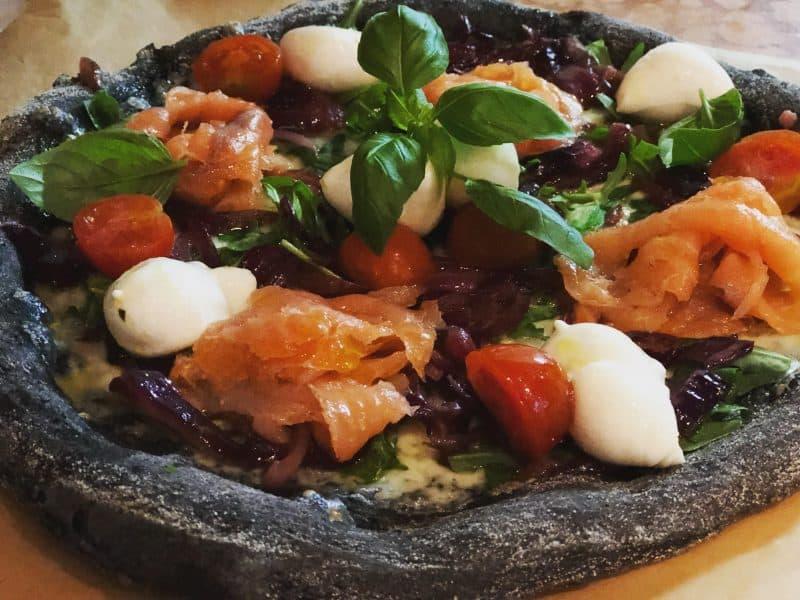 Schwarze Pizza mit Tintenfischtinte, geräucherten Lachs, karamellisierten Zwiebeln und Babybüffelmozzarella